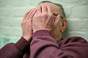 An elderly inmate covers his face to protect his identity while lying relaxing on the bed in his cell in the Vulnerable Prisoners Unit. HM Prison Wandsworth is a Category B men's prison at Wandsworth in the London Borough of Wandsworth, South West London, United Kingdom. It is operated by Her Majesty's Prison Service and is one of the largest prisons in the UK with a population over 1500 people. (photo by Andy Aitchison)