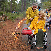 Wilmington Mayor Bill Saffo and Ms. Wheelchair USA 2017 Madeline Delp light the controlled burn demonstration at the Fire In The Pines Festival.