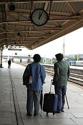 Man and woman looking at clock on railway platform,