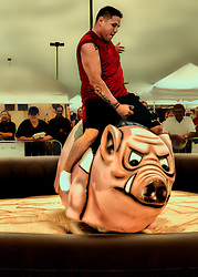 Riding the mechanical pig at Rib Fest to win a prize