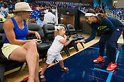 Skylar Diggens of the Dallas Wings high-fives Charlie Muehlhausen, 2, as she returns to the court after half time against the Connecticut Sun during a WNBA preseason game in Arlington, Texas on May 8, 2016.  (Cooper Neill for The New York Times)