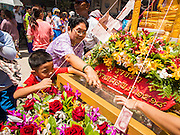 """05 JULY 2014 - BANGKOK, THAILAND: Thais donate money to a float during a parade for vassa. Vassa, called """"phansa"""" in Thai, marks the beginning of the three months long Buddhist rains retreat when monks and novices stay in the temple for periods of intense meditation. Vassa officially starts July 11 but temples across Bangkok are holding events to mark the holiday all week.    PHOTO BY JACK KURTZ"""