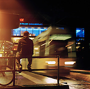 Man sitting on railings at a tram staion near Alexanderplatz in Berlin, Germany
