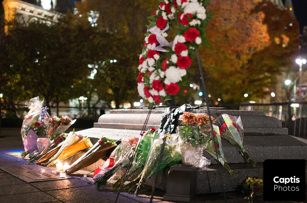 Flowers lay against the cenotaph the night after the fatal shooting of Cpl. Nathan Cirillo. October 23, 2014.