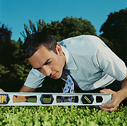 Serious man checking trimmed shrub with level, close-up