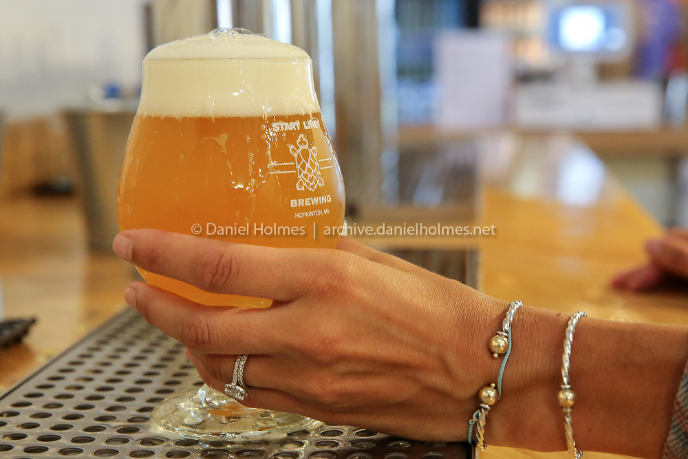 (7/10/19, HOPKINTON, MA) Bartender Stephanie Glenn pours some Hop Load Hazy IPA at Start Line Brewing in Hopkinton on Wednesday. [Daily News and Wicked Local Photo/Dan Holmes]