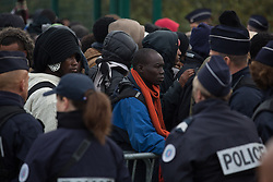 """Dschungel von Calais: Das wilde Fl¸chtlingslager wird ger‰umt und die Fl¸chtlinge in Aufnahmezentren verteilt / 241016 ***Calais, Pas-de-Calais, France - 24.10.2016    <br />  <br /> Refugees line up at the registration center to get in busses. Start of the eviction on the so called îJungle"""" refugee camp on the outskirts of the French city of Calais. Refugees and migrants leaving the camp to get with buses to asylum facilities in the entire country. Many thousands of migrants and refugees are waiting in some cases for years in the port city in the hope of being able to cross the English Channel to Britain. French authorities announced a week ago that they will evict the camp where currently up to up to 10,000 people live.<br /> <br /> <br /> Fluechtlinge stehen vor dem Registrierungscenter um in Busse steigen zu koennen. Beginn der Raeumung des so genannte îJungleî-Fluechtlingscamp in der franzˆsischen Hafenstadt Calais. Fluechtlinge und Migranten verlassen das Camp um mit Bussen zu unterschiedlichen Asyleinrichtungen gebracht zu werden. Viele tausend Migranten und Fluechtlinge harren teilweise seit Jahren in der Hafenstadt aus in der Hoffnung den Aermelkanal nach Groflbritannien ueberqueren zu koennen. Die franzoesischen Behoerden kuendigten vor einigen Wochen an, dass sie das Camp, indem derzeit bis zu bis zu 10.000 Menschen leben raeumen werden. <br /> <br /> Photo: Bjoern Kietzmann"""