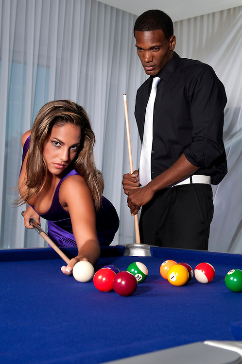 Multiracial couple playing pool at night in upscale place.