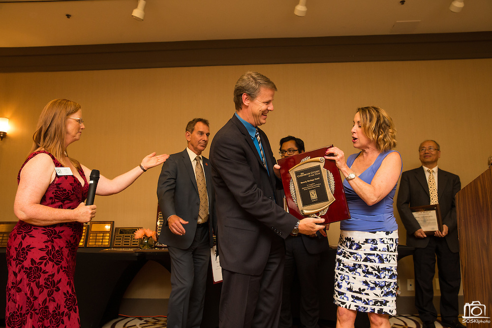 Nina Moore of Robson Homes presents General Manager Greg Magee of Beverly Heritage Hotel with Corporate Citizen of the Year during the Milpitas Chamber of Commerce 59th Annual Awards and Installation Banquet at Sheraton San Jose Hotel in Milpitas, California, on July 28, 2016. (Stan Olszewski/SOSKIphoto)