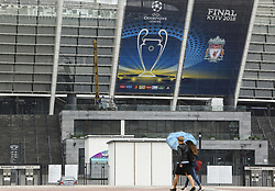 May 13, 2018 - Kiev, Ukraine - Women under the umbrella walk past NSC Olimpiyskiy Stadium covered with banners for the Champions League in Kyiv, Ukraine, May 13, 2018. Kyiv prepares to host UEFA Women's Champions League final between Wolfsburg and Lyon at Valeriy Lobanovskiy Dynamo Stadium on 24 May, 2018 and the UEFA Champions League final match between Real Madrid and  Liverpool at NSC Olimpiyskiy Stadium on Saturday 26 May, 2018. (Credit Image: © Sergii Kharchenko/NurPhoto via ZUMA Press)