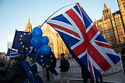 Anti Brexit pro remain demonstrators protest waving European Union and Union Jack flags in Westminster opposite Parliament on the day that Conservative Party MPs triggered a vote of no confidence in the Prime Minister on 12th December 2018 in London, England, United Kingdom.