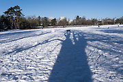 Small figures of people are part of a winter scene in the snow in Canon Hill Park in Moor Green on 25th January 2021 in Birmingham, United Kingdom. Deep snow arrived in the Midlands giving some light relief and fun during the current lockdown for people who simply enjoyed the weather.