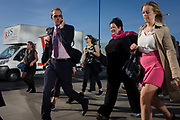 Man admires women while crossing southbound over London Bridge during the evening rush hour. The young man gives the pretty woman a sidways glance as he overtakes her, followed by others walking out of the City of London. There has been a crossing over the Thames here since the Romans first forded the river in the early 1st Century with subsequent medieval and Victorian stone bridges becoming an important thoroughfare from the City on the north bank, to Southwark on the south where transport hubs such as the mainline station gets commuters to the suburbs and satellite towns.