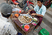 26 FEBRUARY 2008 -- MYAWADDY, MYANMAR: A food stall on the street in Myawaddy, Myanmar (Burma). Myawaddy is just across the Moei River from Mae Sot, Thailand and is one of Myanmar's leading land ports for goods going to and coming from Thailand. Most of the businesses in the town are geared towards trade, both legal and illegal, with Thailand. Human rights activists from Myanmar maintain that the Burmese government controls the drug smuggling trade between the two countries and that most illegal drugs made in Myanmar are shipped into Thailand from Myawaddy.   Photo by Jack Kurtz