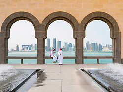 Two local men and skyline of Doha financial district  at the Museum of Islamic Art in Doha Qatar