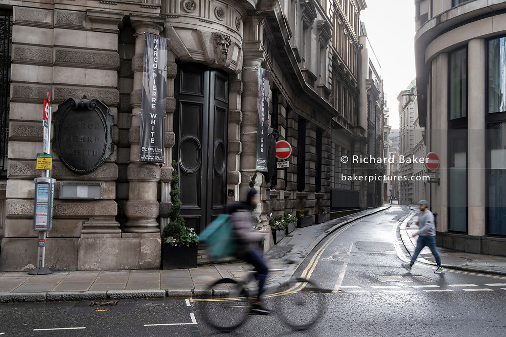 A cyclist and a pedestrian blur across a quiet Threadneedle Street during the third lockdown of the Coronavirus pandemic, in the 'City of London', the capital's financial district, aka The Square Mile, on 2nd February 2021, in London, England.