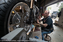 Bill Dodge works on the primary drive of Jim Root's (from the band Slipknot) custom Harley-Davidson FXR in his Blings Cycle shop during Daytona Bike Week 75th Anniversary event. FL, USA. Friday March 4, 2016.  Photography ©2016 Michael Lichter.