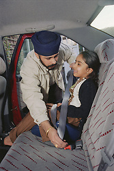 Father fastening daughter into child car seat,
