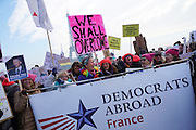 January, 21st, 2017 - Paris, Ile-de-France, France: Women Democrats Abroad with 'We shall overcome' placard at Trocadero with Eiffel Tower behind. Thousands of protesters in Paris join anti-Trump Women's March around the world.