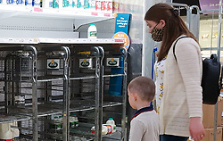 © Licensed to London News Pictures. 31/07/2021. London, UK. A woman and a child look at empty shelves of milk in Sainsbury's, north London. The UK's biggest milk processor, Arla Foods UK, has said that about 600 individual stores out of the 2,400 that it routinely supplies missed a delivery due to the pingdemic and a lack of lorry drivers. The pingdemic has seen staff shortages at supermarkets, resulting in less stock making its way to supermarket shelves. Photo credit: Dinendra Haria/LNP