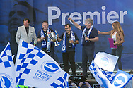 Paul Barber, Tony Bloom, and Martin Perry on stage with the trophy during the Brighton & Hove Albion Football Club Promotion Parade at Brighton Seafront, Brighton, United Kingdom on 14 May 2017. Photo by Phil Duncan.