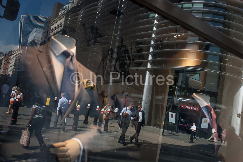 Menswear suits are on sale in a retailers window, with reflections of everyday City life in the background, on 24th August 2016, on Cannon Street, in the City of London, UK. Men in shirtsleeves walk across the busy road running across the capitals financial district, founded by the Romans in the first Century.