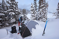 A skiier breaking camp in early morning after a heavy snow overnight.   Near Denny Lake, Beartooth Mountains, Montana.