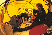 American mountaineers Kitty Calhoun and Jay Smith prepare a meal in their tent at Advance Base Camp during an attempt to climb the north face of Thelay Sagar in the Garwal Himal of India.