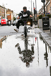 © Licensed to London News Pictures. 25/09/2019. London, UK. A cyclist rides the bike through the flood on Green Lanes in north London caused by heavy overnight downpour. Photo credit: Dinendra Haria/LNP