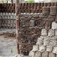 Africa, Botswana, Okavango Delta. Village homes and structures in the Okavango Delta - recycled cans are used within the dung and mud walls to insulate.