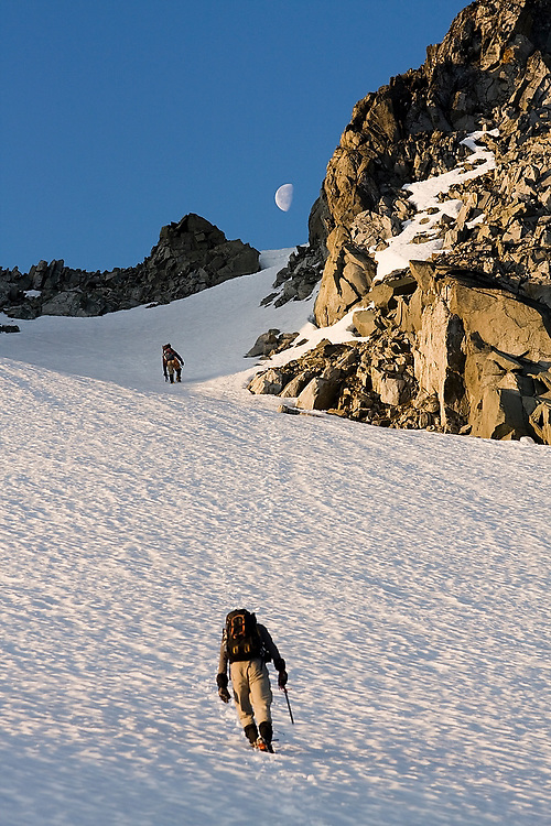 Climbers Jim Prager and Obadiah Reid ascend towards the moon and the NE Arete of Wedge Mountain in Garibaldi Provincial Park, British Columbia, Canada on June 14, 2009.