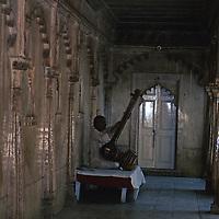 Asia, India, Uttar Pradesh, Fatehpur Sikri. A man plays a sitar in the halls of Fatehpur Sikri.
