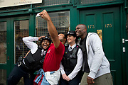 Notting Hill Carnival 2016 Childrens Day. A man takes a selfie photo with two policewomen and his friend.