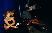 Young adolescent couples kiss and cuddle in a dark corner of a Gatecrashers' Ball in London, England. Three boys and girls dressed in formal evening-wear have been consuming alcohol during the evening and are groping and snogging. The Gatecrasher Ball was an eighties phenomenon conceived by Edward Ormus Sharington Davenport whose parties catered for Public School students. Labled as excessive and out of control events, Davenport charged <br /> £14 a ticket, for often 3,000 kids although he was later fined for tax evasion.