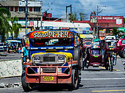 """31 JANUARY 2018 - LEGAZPI, ALBAY, PHILIPPINES: """"Jeepneys"""" on the streets of Legazpi, Philippines. Jeepneys are the iconic Filipino form of mass transit. Originally based on the World War II Willy's Jeep, they are now are entirely a Filipino vehicle with the engine and drive train usually from Japanese light trucks.         PHOTO BY JACK KURTZ"""