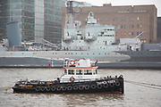 Tugboat moored on the River Thames in line with ex-military vessel HMS Belfast on 22nd January 2020 in London, England, United Kingdom. A tugboat or tug is a type of vessel that maneuvers other vessels by pushing or pulling them either by direct contact or by means of a tow line.