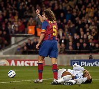 Photo. Jed Wee, Digitalsport<br /> FC Barcelona v Chelsea, UEFA Champions League, 23/02/2005.<br /> Chelsea's Didier Drogba (R) lies injured as Barcelona's Carlos Puyol asks referee Anders Frisk to book him for a challenge on goalkeeper Victor Valdes.