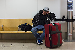 © licensed to London News Pictures. London, UK 31/10/2012. A passenger from Heathrow to the US waiting for his flight to return normal in the check-in area at Heathrow Terminal 1 after Hurricane Sandy hit the east coast in the US. Photo credit: Tolga Akmen/LNP