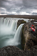 Woman photographing Godafoss waterfall in northern Iceland