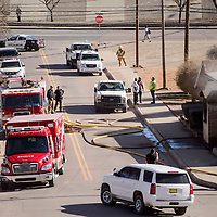 Gallup firefighters, police and emergency responders gather at the scene of a home fire at First Street and Wilson Avenue in Gallup Thursday.