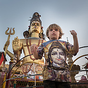 Boy tries to imitate the pose of a God (Shiva). Omkareshwar.
