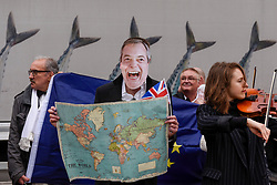© Licensed to London News Pictures. 29/03/2017. London, UK.  A man wears a Nigel Farage mask as he takes part in a Pro-Europe protest, outside the Houses of Parliament.  Today, is the day that Article 50 is formally triggered, with a handwritten letter bearing the Prime Minister's signature being delivered to the European Union today. Photo credit : Stephen Chung/LNP