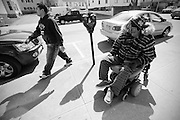 A man walks by Carlos as he makes his way down Main St. in Fall River to meet his father at the club.  Carlos Raposa, 49, has lived with diabetes since he was 21 years old.  Due to some complications heightened by the disease, Mr. Raposa lost both legs below the knees.  As his condition has worstened over the years Carlos has had greater difficulty dealing with his condition.  Increasingly, Carlos has fallen greater into depression and has turned to smoking and drinking to deal with it.  What used to be monthly visits to the hospital has turned into weekly excursions with ever longer stays in hospital.  Family members have become ever more worried about Carlos' drop in weight and his inability to move on his own any longer.  For someone who was an athletic figure, Carlos has become a shadow of his former self.