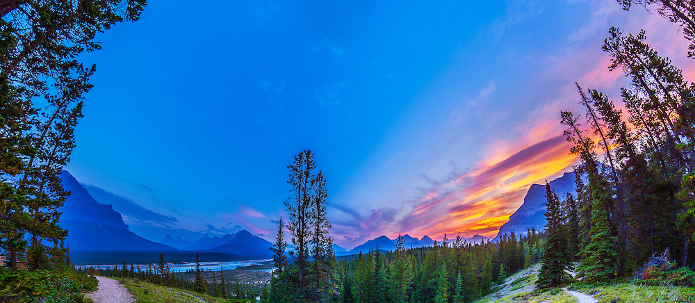A 180° panorama looking south at sunset from the Howse Pass Viewpoint near Saskatchewan River Crossing on the Icefields Parkway at the David Thompson Highway 11 intersection. The scene includes the North Saskatchewan River, the peaks of the Continental Divide to the south including Mt. Cephren, and Mt. Murchison at left. Howse Pass, site of the famous passage used for a time by David Thompson in the fur trade in the early 1800s, is at right. The river plain here was also a sacred site for the Pikanii First Nation people. I shot the frames for this 6-section panorama August 12, 2014 using the Canon 5D MkII and Rokinon 14mm lens, portrait orientation, and stitched them with PTGui. The layout would make for a great 2-page spread in a magazine, with sky space for headlines and type.