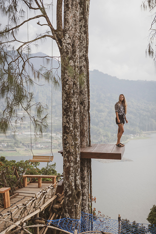 Bali, Indonesia - September 22, 2017: A young woman visiting Bali takes in the beautiful view from a platform high above Lake Buyan.