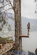 A young woman visiting Bali takes in the beautiful view from a platform high above Lake Buyan.