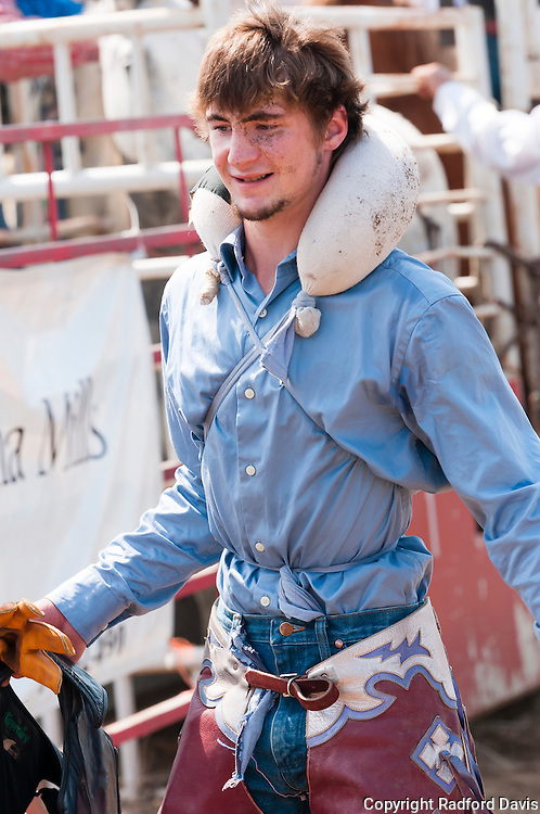 A cowboy with a neck pillow to prevent injury during his time atop a bucking horse.