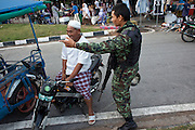 """Sept 26, 2009 -- PATTANI, THAILAND:  A Thai soldier directs a Muslim man on a motorcycle to a parking area during a security operation near Krue Se Mosque in Pattani, Thailand, Sept. 26. Thailand's three southern most provinces; Yala, Pattani and Narathiwat are often called """"restive"""" and a decades long Muslim insurgency has gained traction recently. Nearly 4,000 people have been killed since 2004. The three southern provinces are under emergency control and there are more than 60,000 Thai military, police and paramilitary militia forces trying to keep the peace battling insurgents who favor car bombs and assassination.   Photo by Jack Kurtz / ZUMA Press"""