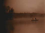 Two men fish in a foggy lake at sunrise