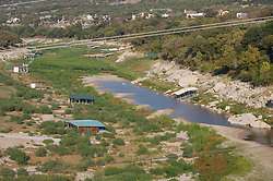 Pedernales River during drought conditions. Boat houses on dry ground.
